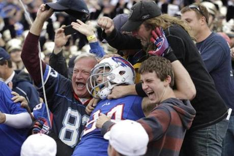 Buffalo TE Scott Chandler celebrated his touchdown catch with fans during the first half .